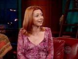 Alyson Hannigan dans une robe violette regarde son interlocuteur