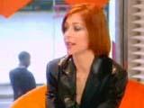 Alyson Hannigan habillée de noir sur le canapé orange qui rappelle la couleur de ses cheveux