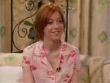 Alyson Hannigan vêtue d'une chemise rose dans un décor un peu vieillot